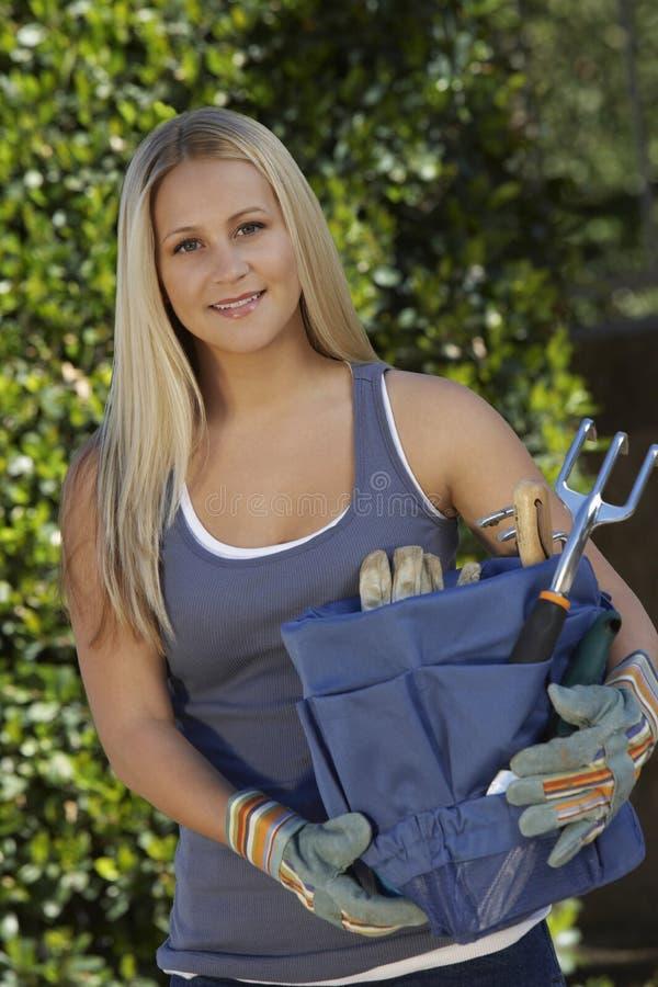 Jovem mulher que guardara o conjunto de ferramentas de jardinagem foto de stock royalty free