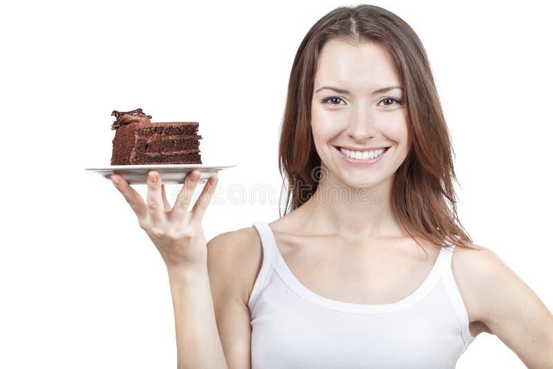 Jovem mulher que guardara a parte de bolo de chocolate fotos de stock