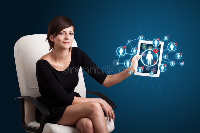 Jovem mulher que guardara a tabuleta com ícones sociais da rede fotos de stock