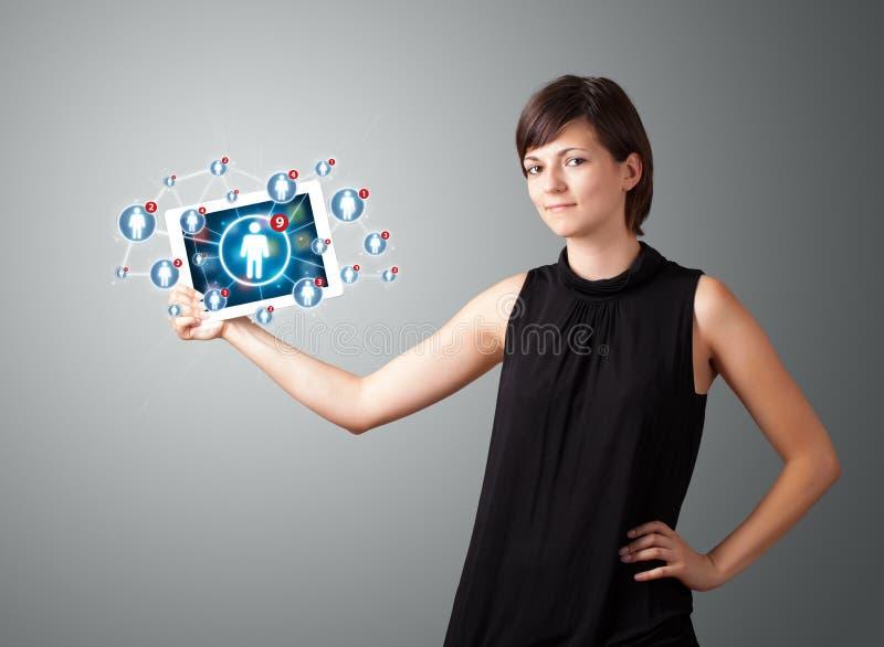Jovem mulher que guardara a tabuleta com ícones sociais da rede fotografia de stock royalty free