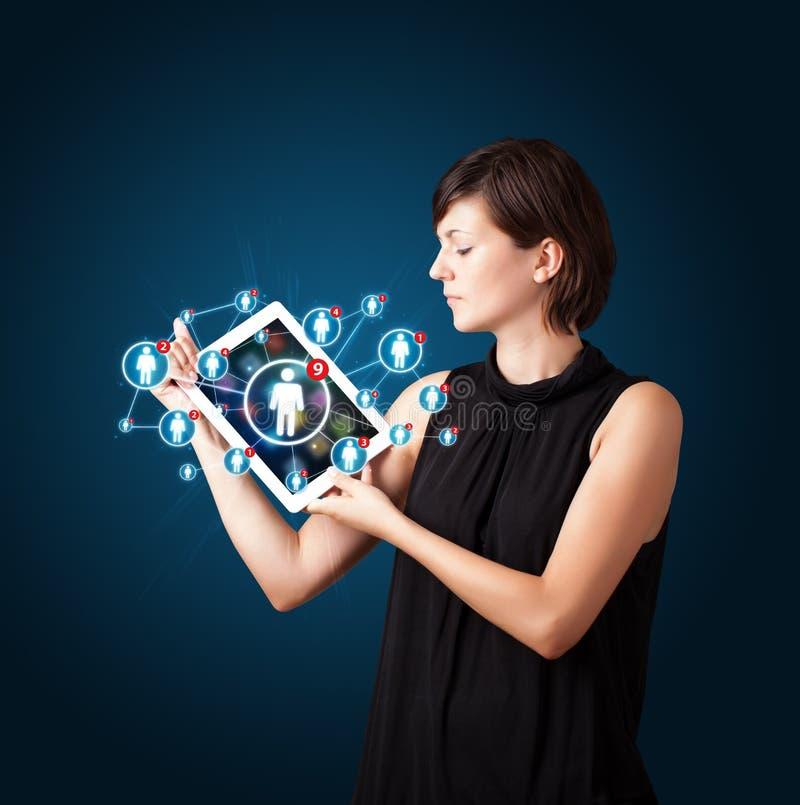 Jovem mulher que guardara a tabuleta com ícones sociais da rede foto de stock royalty free