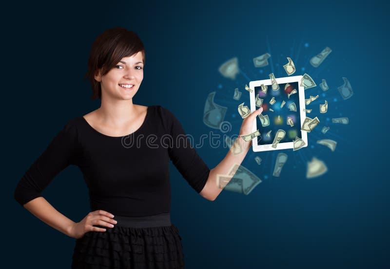 Jovem mulher que guardara a tabuleta com dinheiro fotografia de stock
