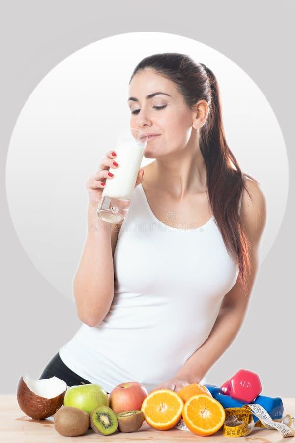 Jovem mulher que guardara um vidro do leite fotografia de stock