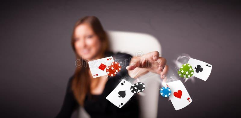 Jovem mulher que joga com cartões e microplaquetas do póquer fotos de stock royalty free