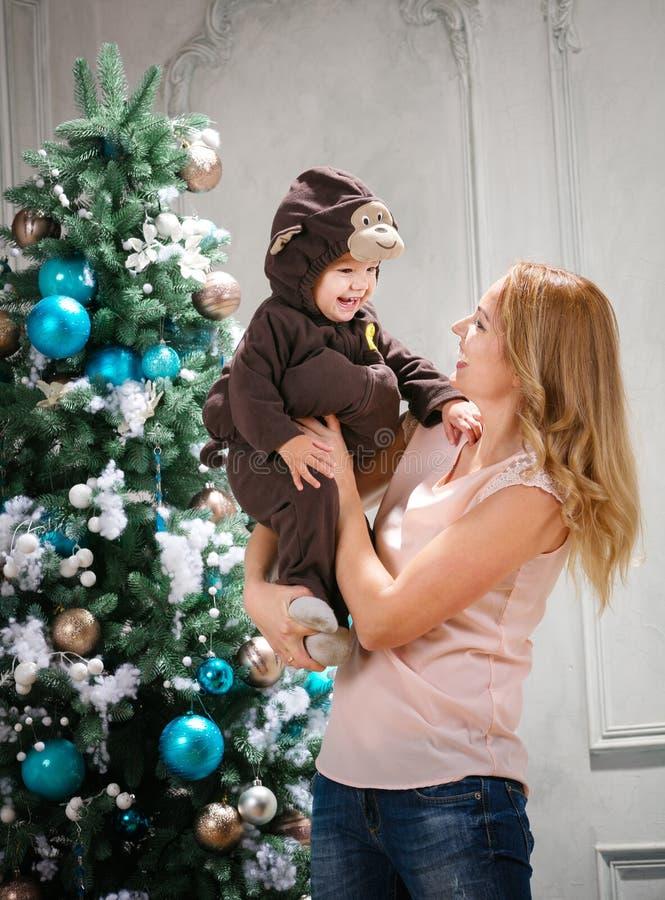 A jovem mulher que joga com filho pequeno vestiu-se no traje do macaco fotografia de stock