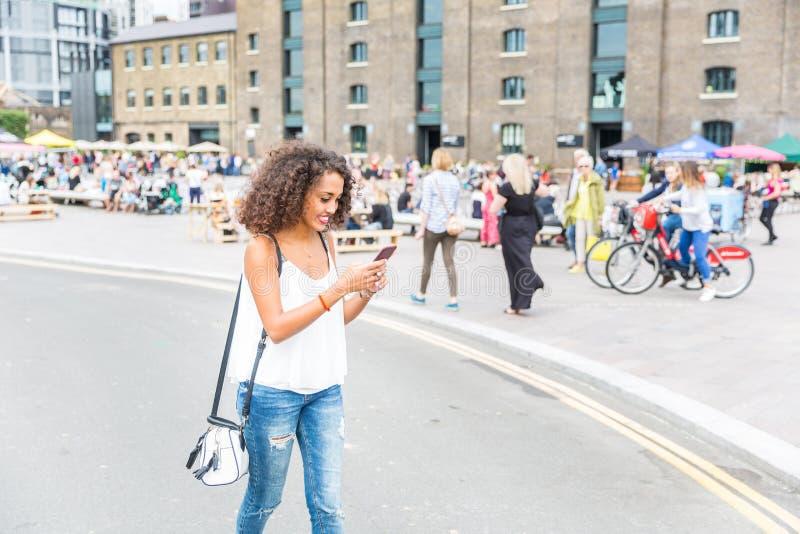 Jovem mulher que joga com jogo aumentado da realidade em Londres foto de stock royalty free