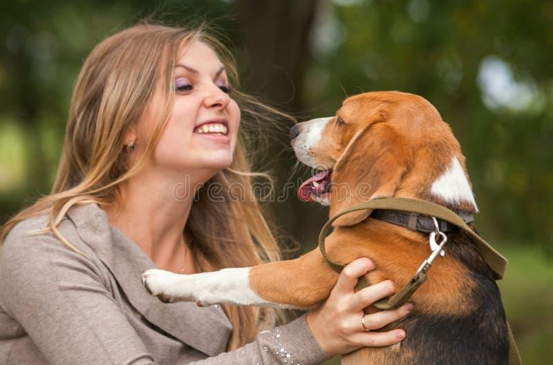 Jovem mulher que joga com seu cão imagem de stock