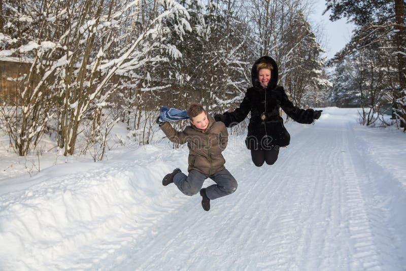 Jovem mulher que joga com um rapaz pequeno em um parque nevado foto de stock