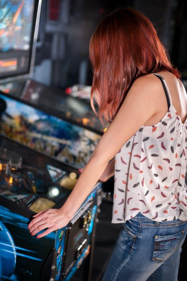 Jovem mulher que joga na máquina de pinball fotografia de stock royalty free