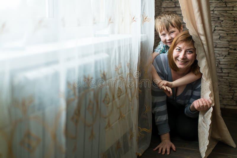 Jovem mulher que joga na sala com seu filho pequeno Família fotos de stock royalty free