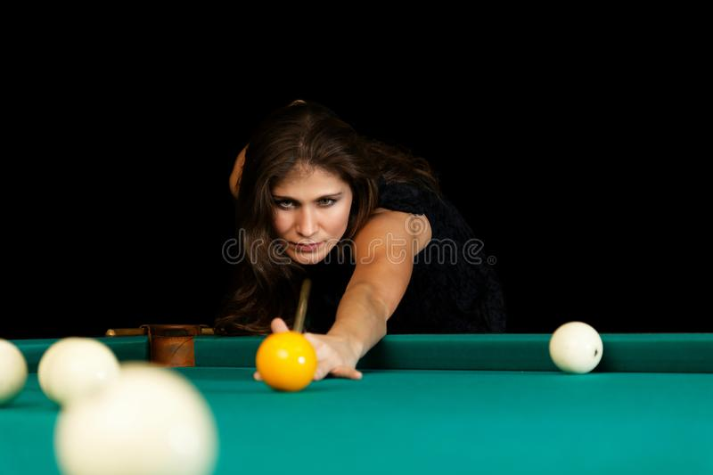 Jovem mulher que joga o bilhar Fundo preto imagens de stock royalty free