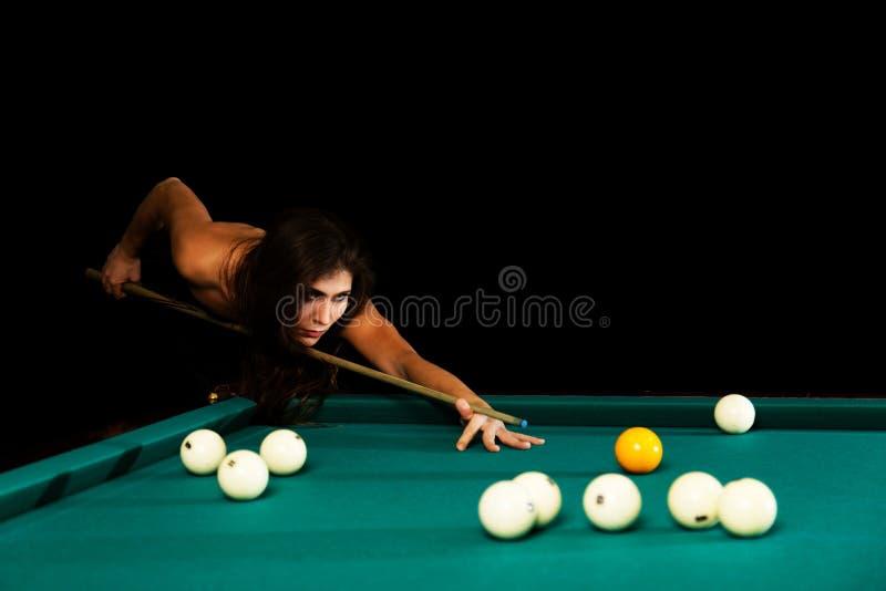 Jovem mulher que joga o bilhar Fundo preto fotos de stock royalty free
