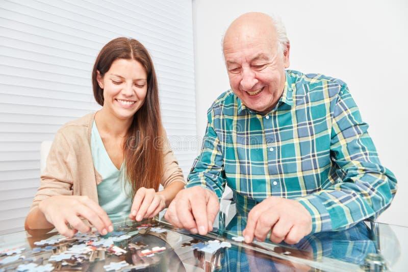 Jovem mulher que joga o enigma com sênior imagem de stock