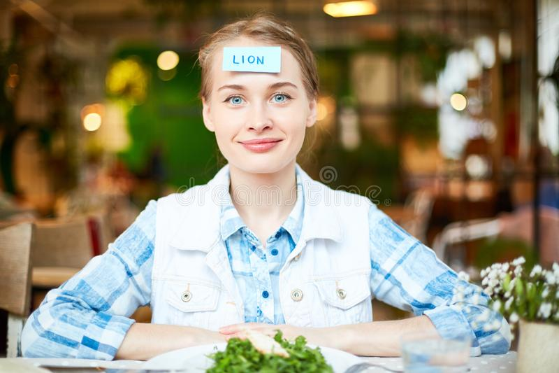 Jovem mulher que joga o jogo com os amigos no restaurante imagem de stock