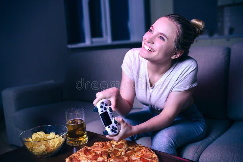 Jovem mulher que joga o jogo na noite Modelo alegre positivo agradável que joga o jogo com gamepad Comida lixo e cerveja na tabel imagem de stock royalty free