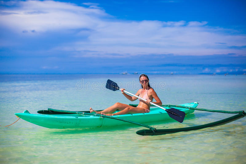 Jovem mulher que kayaking apenas na claro mar azul imagens de stock
