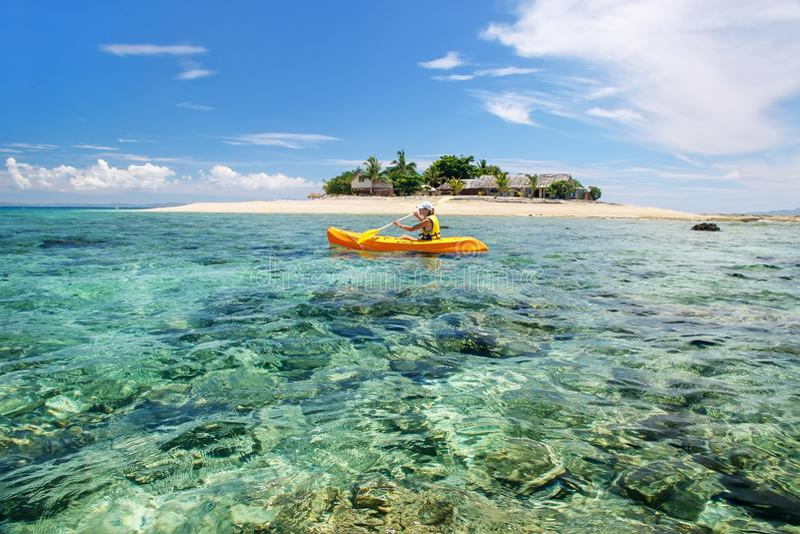 Jovem mulher que kayaking perto da ilha de mar sul, grupo de ilhas de Mamanuca, Fiji fotos de stock