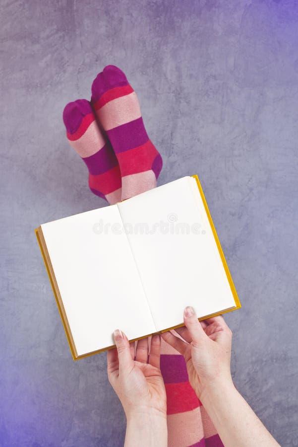 Jovem mulher que lê o livro de Pulp Fiction fotografia de stock