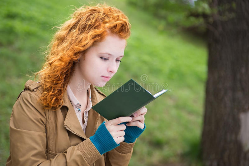 Jovem mulher que lê um livro. fotos de stock