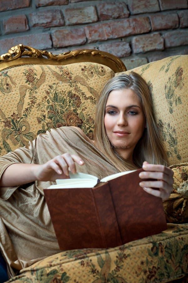 Jovem mulher que lê um livro em casa no sofá fotos de stock