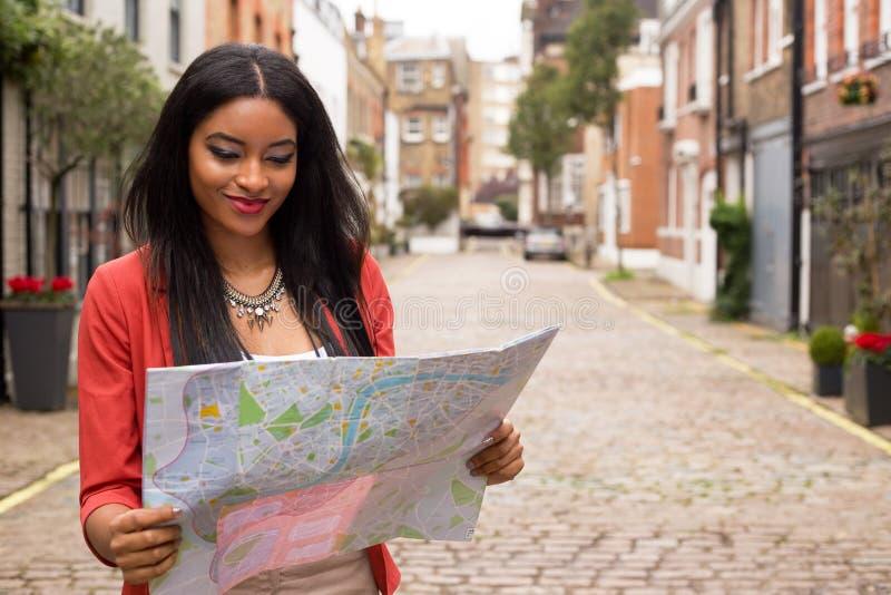 Jovem mulher que lê um mapa fotos de stock royalty free