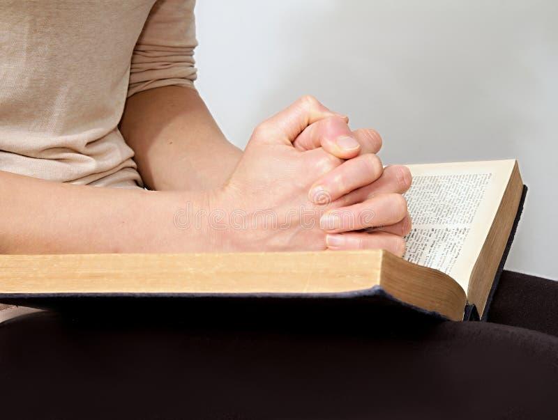 Jovem mulher que lê uma Bíblia na paz e o quiete e rezar foto de stock royalty free