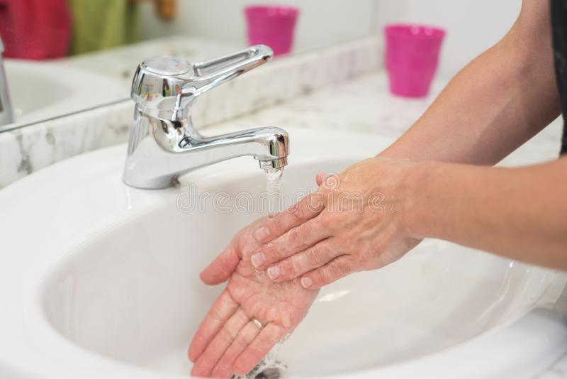 Jovem mulher que lava suas mãos fotografia de stock