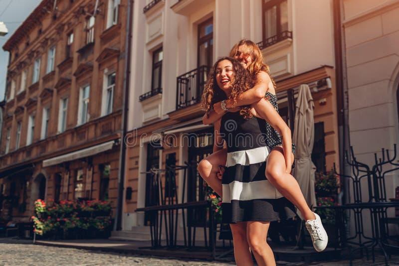 Jovem mulher que leva seu melhor amigo nela para trás na rua da cidade Meninas adolescentes felizes que riem e que têm o divertim imagens de stock