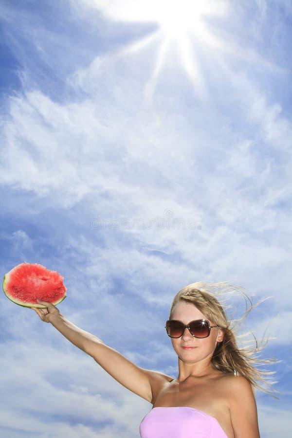 jovem mulher que levanta com a melancia contra wi do céu azul foto de stock royalty free