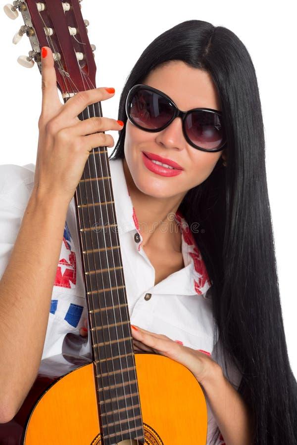 Jovem mulher que levanta com uma guitarra fotografia de stock