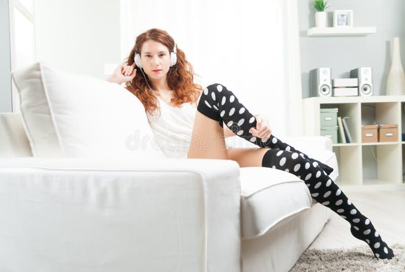 Jovem mulher que levanta em seu sofá e que escuta a música imagem de stock royalty free