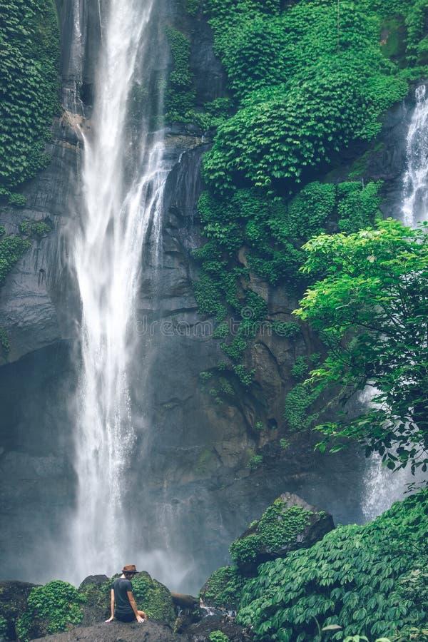 Jovem mulher que levanta em uma grande cachoeira de Sekumpul na floresta úmida profunda da ilha de Bali, Indonésia fotografia de stock