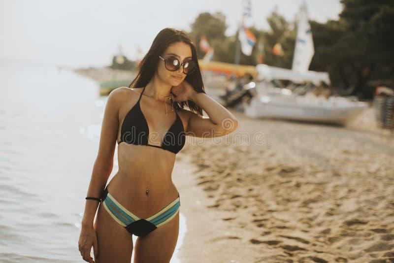 Jovem mulher que levanta na praia em um biquini fotos de stock royalty free