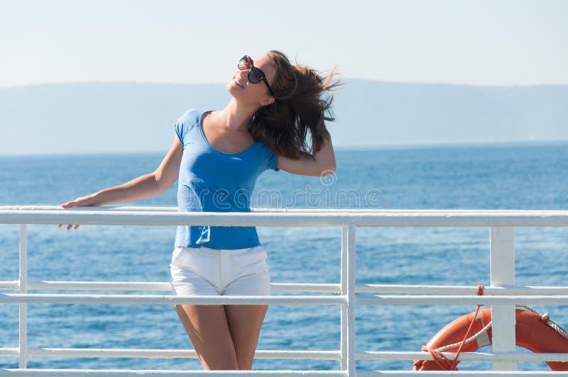 Jovem mulher que levanta no navio de cruzeiros durante férias de verão fotografia de stock