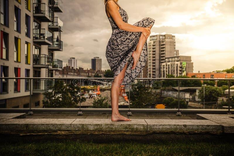 Jovem mulher que levanta seu pé na parte superior do telhado foto de stock