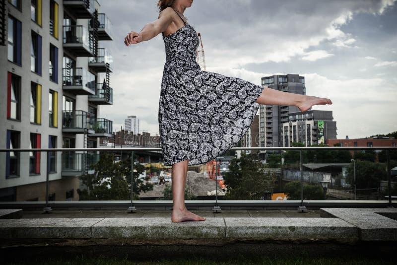 Jovem mulher que levanta seu pé na parte superior do telhado fotografia de stock