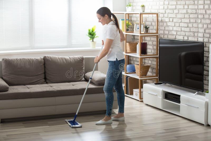Jovem mulher que limpa o assoalho de folhosa fotografia de stock