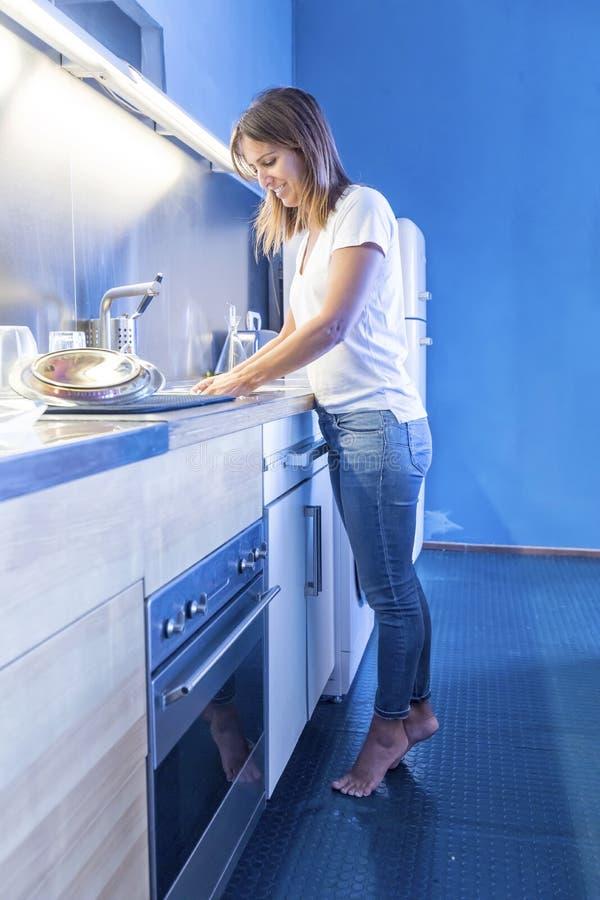 Jovem mulher que limpa o dissipador na cozinha imagem de stock