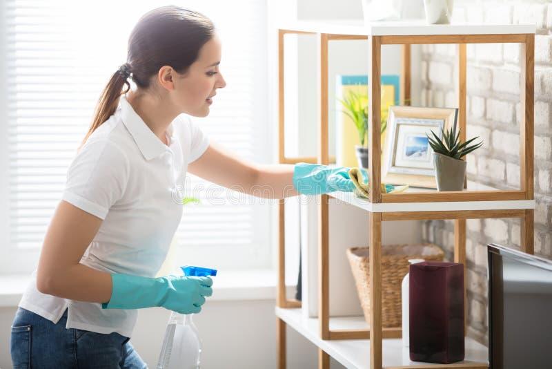 Jovem mulher que limpa a prateleira na casa fotografia de stock