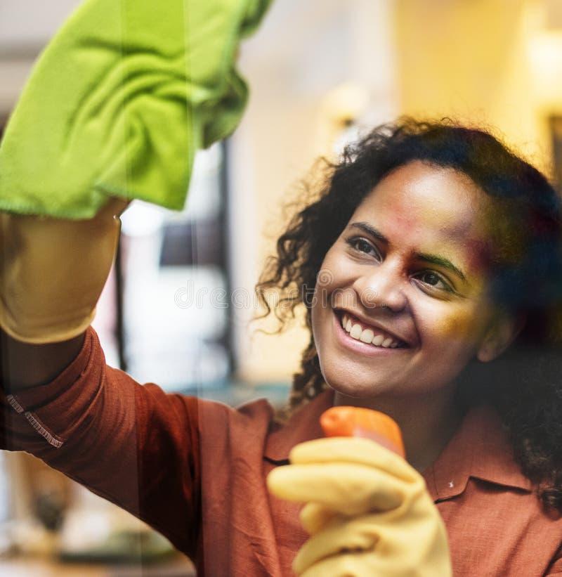 Jovem mulher que limpa um conceito da empregada da janela imagens de stock