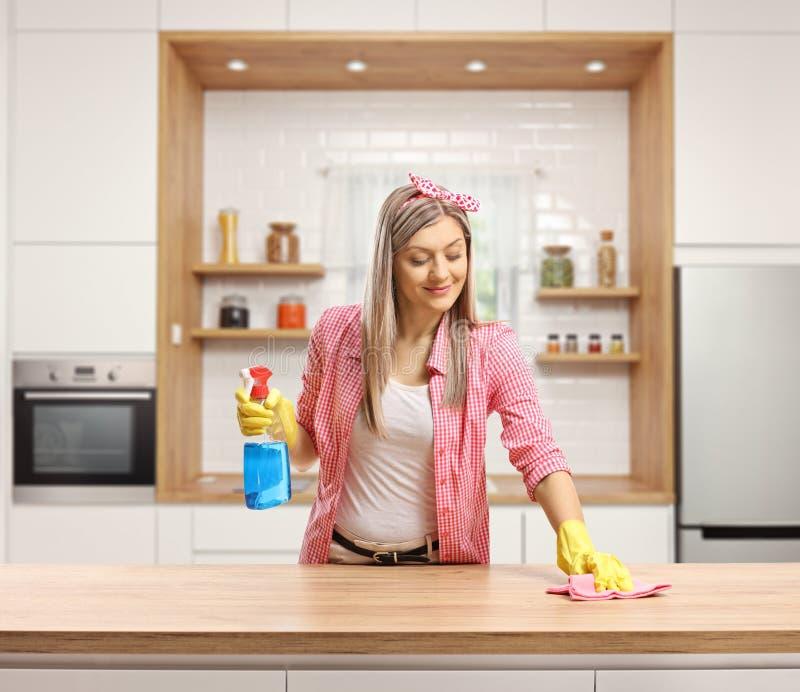 Jovem mulher que limpa uma parte superior contrária de madeira em uma cozinha fotografia de stock