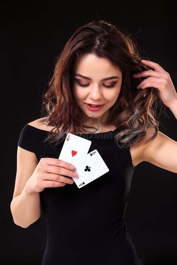 Jovem mulher que mantém cartões de jogo contra um fundo preto fotos de stock