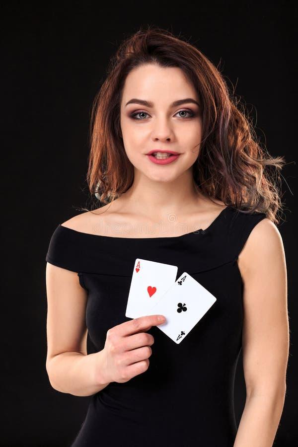 Jovem mulher que mantém cartões de jogo contra um fundo preto imagem de stock royalty free