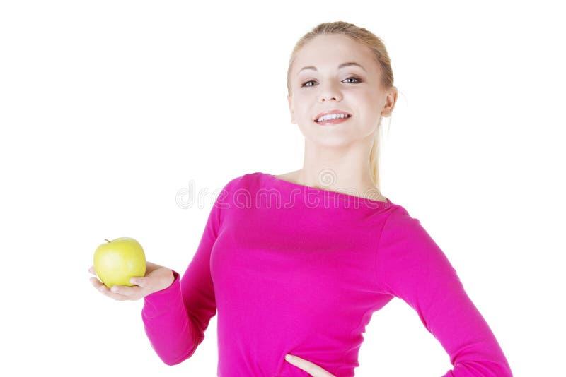 Jovem mulher que mantém a maçã fresca verde disponivel. fotos de stock royalty free