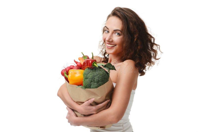 Jovem mulher que mantém o saco de compras de papel do mantimento completo de legumes frescos Conceito saudável comer da dieta fotos de stock royalty free