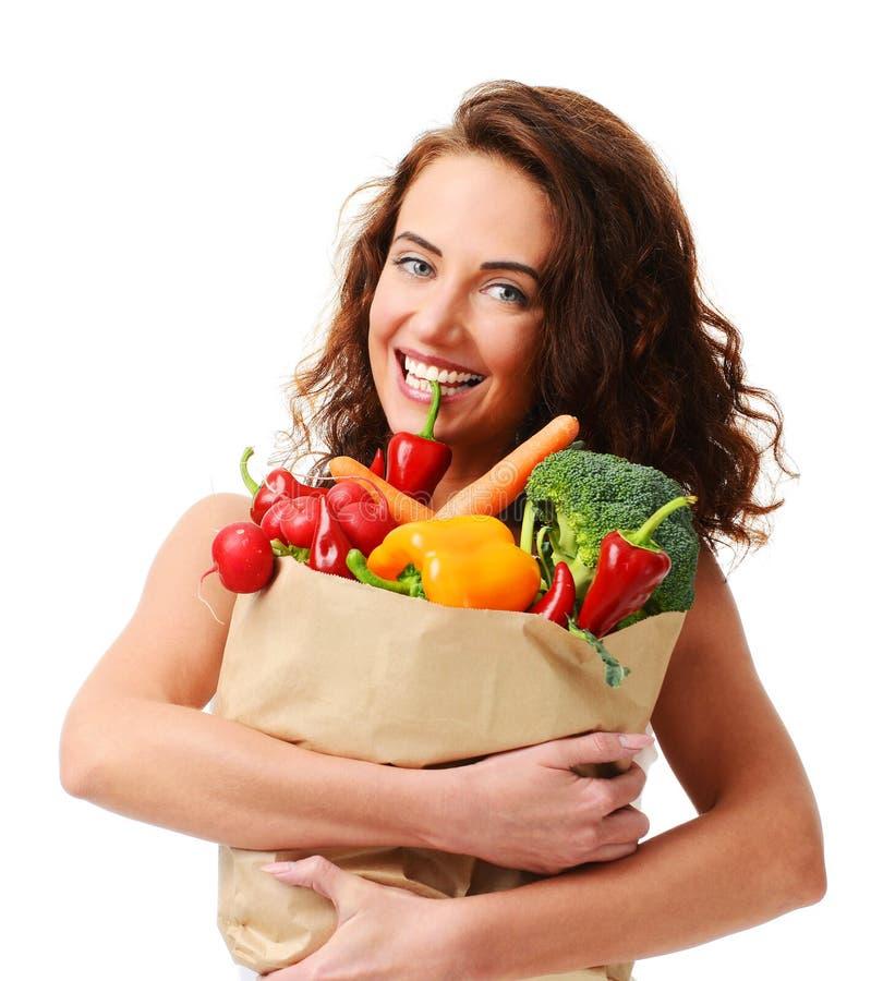 Jovem mulher que mantém o saco de compras de papel do mantimento completo de legumes frescos Conceito saudável comer da dieta imagens de stock royalty free