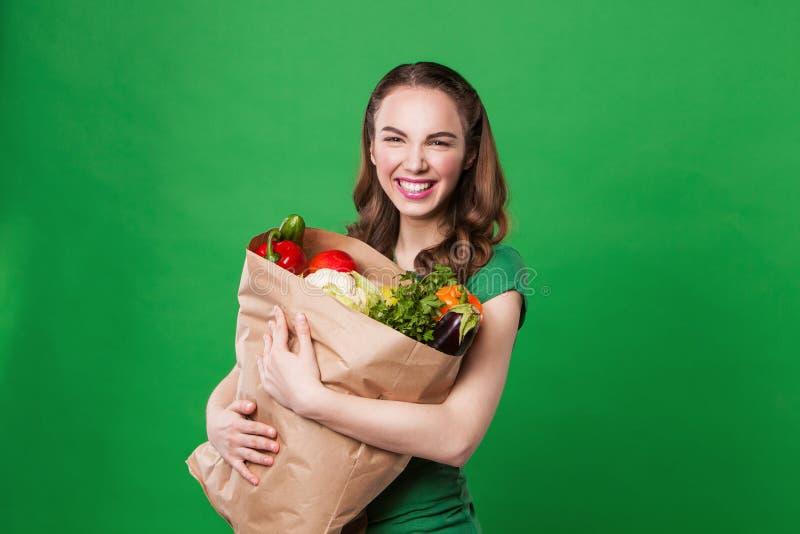 Jovem mulher que mantém um saco de mantimento completo de fresco foto de stock