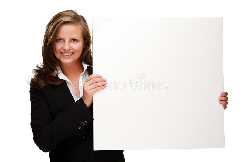 Mulher atrativa nova atrás da placa vazia no fundo branco fotos de stock