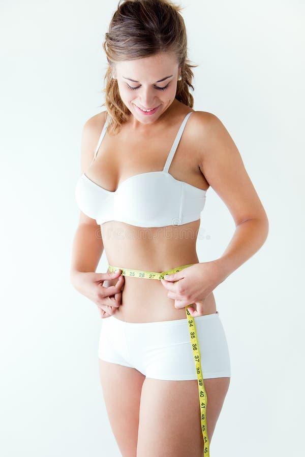 Jovem mulher que mede sua cintura pela medida da fita imagens de stock royalty free
