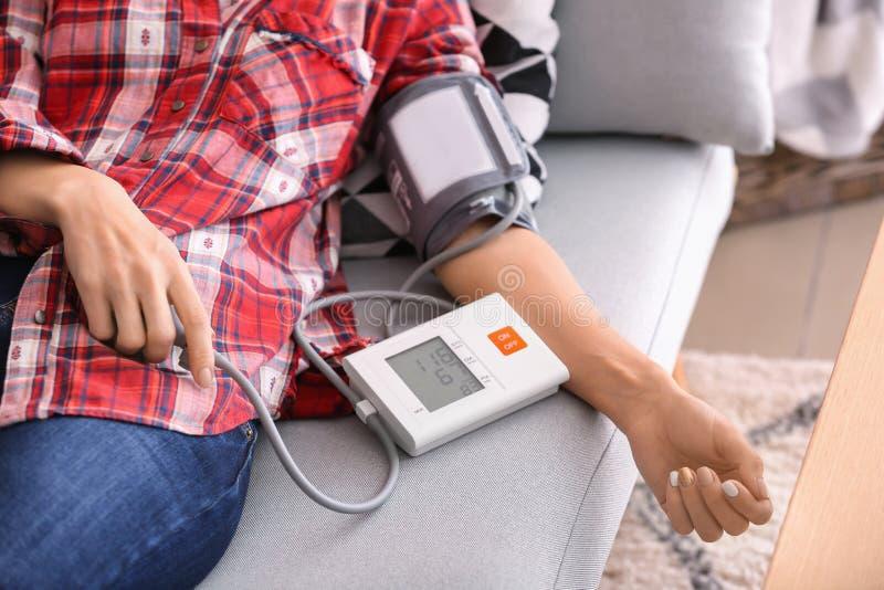 Jovem mulher que mede sua pressão sanguínea em casa foto de stock royalty free